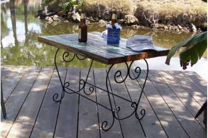 When we replaced the old, rotted dock with a new one, we hated to discard the old dockboards. A recycled planter stand base finds new life as table legs.