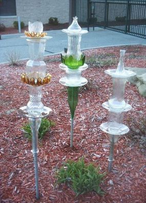 I stacked various glass pieces and glued together with epoxy.  The upside down vase on the bottom slips over a pipe pounded into the ground.