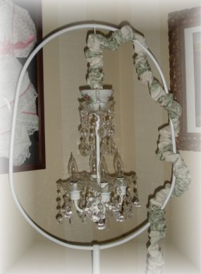 Homemade petite chrystal chandelier on a vintage birdcage stand.