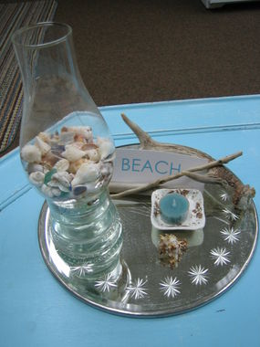 This was a birthday gift that my friend, Diane created and gave to me.   She used a hurricane glass chimney, a vintage telephone insulator, and I added my own shells and beach glass.