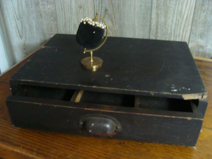 A neat little drawer and a pin cushion on top.