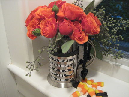 A black and white vase teamed with some yummy-yet-inexpensive deep orange spray roses is an elegant way to say happy Halloween!