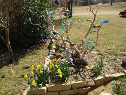 My little bottle tree has seen better days.  This past spring I staked it with a T-post, hoping to get another year of joy from it. I also placed a windchime on one branch.  Now I can hear when it talks to me!