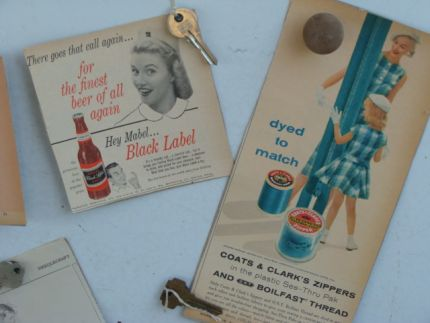 Just for fun (and a little decoration)...vintage magazine advertisements (some of them are so funny!)  (mounted on posterboard), and hung on the metal table top with magnets that we decorated with keys, knobs, etc...