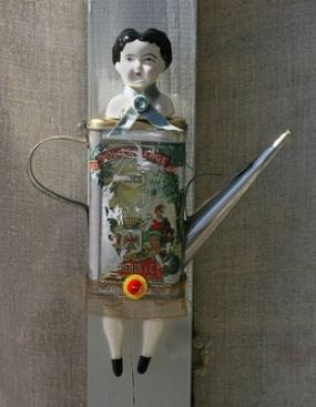 This is Olive, she is fashioned out of an old olive oil can, doll parts, vintage buttons and a bit of old screen.