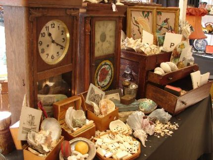 display of old clocks, shells, boxes and photos of old houses