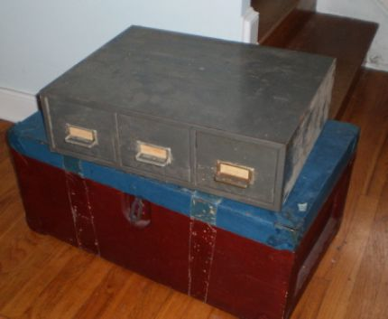 A wood trunk being thrown out and a dusty, metal file cabinet tucked deep down in the basement.