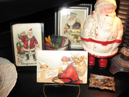 Old paper mache Santa with some of my collection of Santa postcards. The one postcard is sitting on a old lamp part turned upside down.