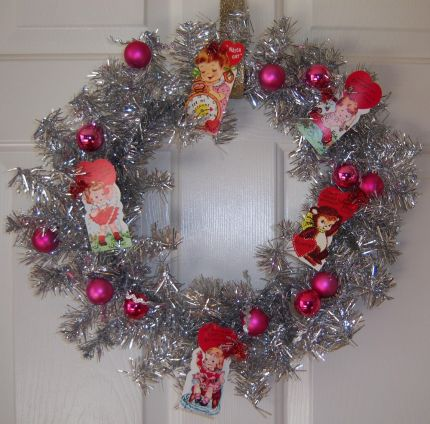 Tinsel wreath form embellished with vintage paper valentines and pink balls.