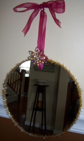 Round mirror trimmed with wired tinsel.  Hung with a ribbon and a vintage brooch.