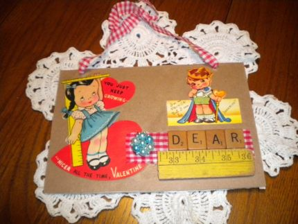 vintage cigar box top, brown paper, vintage valentines, scrabble tiles, scrap yardstick, and a vintage clip earring