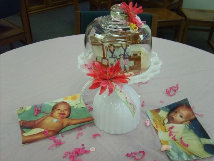 Each centerpiece was a vase turned upside down, a plate, cheese, dome, confetti, and more baby pictures,