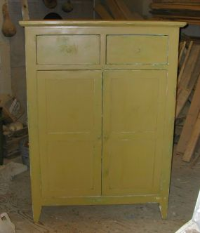 The finished cupboard painted a honey mustard color.