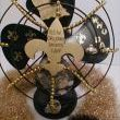 This is an old fan that was rusty and non working. (ok, I know I should have kept the rust but I have another one). I sprayed it black cause thats one of our colors. My husband cut out the fluer de lis and Louisiana out of wood. I spray painted them gold and glued them on. Mardi Gras beads are also glued on