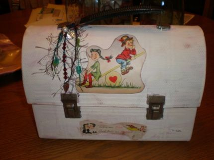 Found a rusty lunch box/pail at an estate sale. Painted it shabby chic. Added some vintage beads, yarn and charms……