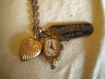 heart locket, toy watch face, and a vintage tag from Penna Watch Case Co., and a tiny key