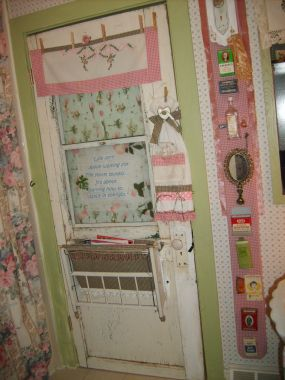 100 year old door, 1/2 doll crib for magazines clothespinned towel with tea set, The pink board next to the door was a 6 foot fence board, covered it to match, hot glued all of my vintage treasures to it.