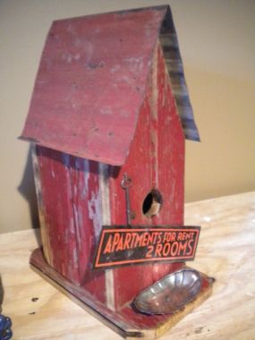 I found this birdhouse at a flea market....but it needed a little something-something...so I added the metal apartments for rent sign, a silverplate soap dish for the birdseed, and an old key. I think any bird would love to move right in