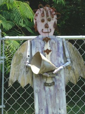 This yard art angel has not found a permanent home in the yard yet, she has been moving around trying to find a place to rest. She is made from reclaimed wood, hair is from bed springs, legs are spindels and arms are from an old chair.