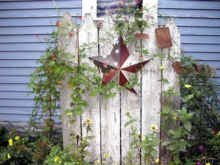 I picked up this old fence piece at auction.  Thought it would make a good centerpiece for my flower garden.  I painted the barn star and add the odd gardening pieces as I find them.