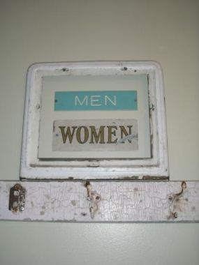 2 vintage bathroom signs framed inside of half of an old heat vent from a house.