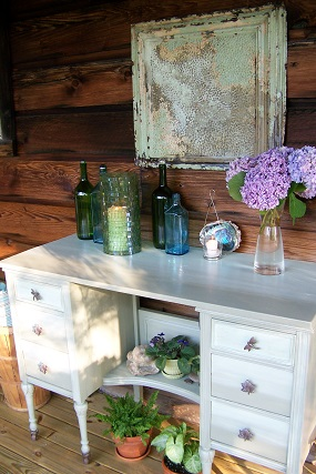With a coat of weather resistant paint, new drawer pulls and a flat board for the top - an old waterfall style vanity is transformed into a functional serving/storage area for the back porch.  The drawers provide plenty of space to stash grilling supplies, napkins, cutlery, candles, and games.