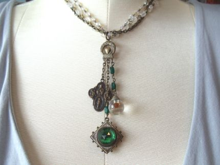 This beautiful necklace is an assemblage of a  vintage brass  chain,antique glass bead chain and vintage AB rosary  beads. Hanging from  the chain is a brass finding with a religious  medal, old glass ball  charm and a wonderful emerald green glass faceted  button attached to an  antique religious icon there is a small coin  attached to the back of the  icon. This piece measures 15 and the  charms hang 3 1/2 from the  chain.