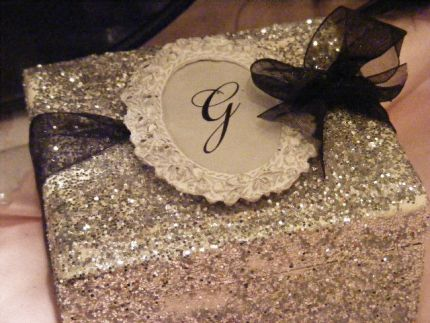 An old frame turned into a monogrammed tag atop a glittered thrift store box.