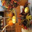 A 2 tier rustic riser holds fall leaves, flowers, a small yellow dipping bowl with a tea candle & a sun flower candle holder with a tea cancle. to give height