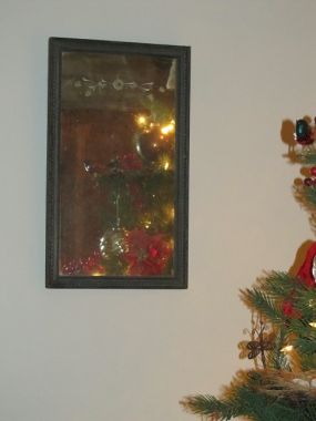 I purchased this old mirror about 18 years ago from a garage sale.  This year I decided to use it close to the Christmas Tree, and it becomes a reflecion art piece showing the reflection of a section of the tree adorned with red, gold ornaments.