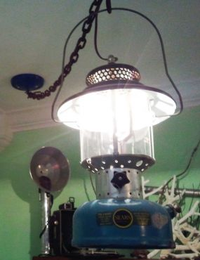 Here is the old Sears Lantern, shedding light on our beach room and the curio shelf behind it. See my post Me, my shelf, and I.