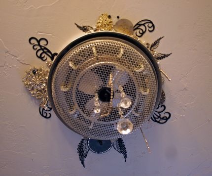 the ceiling fan/heater in the bathroom: a new addition: a round heater that went into a square hole...   To fix the gaps I used old rhinestone jewelry, crystals, glitter & sparkle.  My industrial version of a crystal chandelier :)