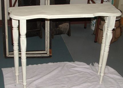 Leaf off an old found table, old rail spindles added for legs, painted with a white milk paint and glazed with a watered down gray.
