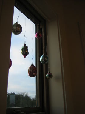 I hung these ornaments with a tension rod and thin wire at varying lengths.