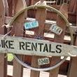 Here is a sign I painted (I think the wood is an old pelt stretcher); mounted it on a rusty bicycle wheel, and added some vintage bicycle license plates (which were purchased with cereal box tops in the 60s...).  And, now were ready to rent some bikes!!  (Hmmm...gotta find a couple old tandems, that would be great!  Yep!!)