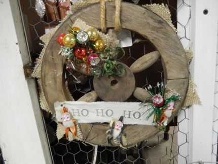 Ho Ho Ho..its an old wooden wheel spreading some Christmas cheer!  (I just love the little vintage Santas!)