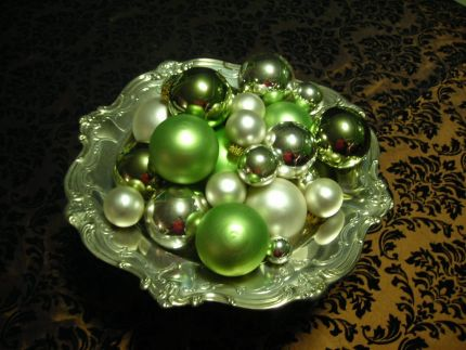 Silver serving piece with green, silver and cream Christmas balls.