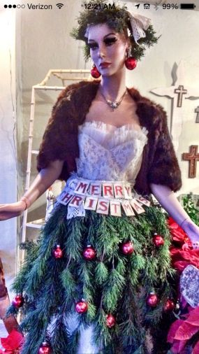 Manniquin window display adorned with a skirt and crown of Christmas tree greens. She has a vintage mink stole and vintage purse and jewelry. Merry Christmas
