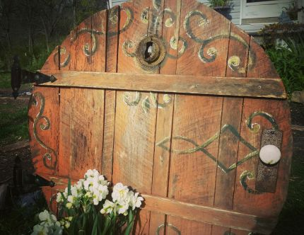 We used old boards and cut into a circle then secured it together with a found round thing.  For the peep whole we used a rusty latern top to cover a naturally occurring knot hole. Last we salvaged decorative hinges, and an old door know with plate.