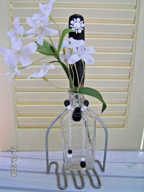 Black wood handled masher, an antique glass bottle, some vintage and new glass beads, and a vintage white earring tops this off.