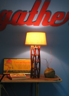 Heres an overall shot of my lawnmower blade lamp. I decided it would look good up against my blue wall shining up onto the metal GATHER. It is sitting on an old hospital gurney, but thats for another post... Regarding the gather sign... it is new and was purchased via the Sundance catalog by Santa for my Christmas present this past holiday.